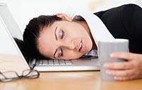 Признаки и причины синдрома хронической усталости - женщина заснула на рабочем месте.