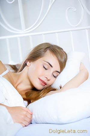 женщина спит правильным сном по фен-шую на светлой кровати