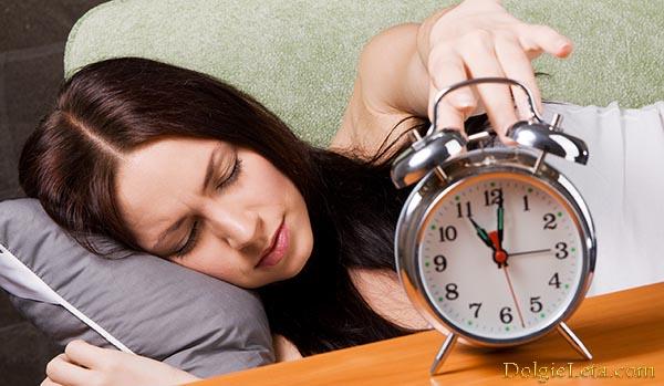 женщина выключает будильник