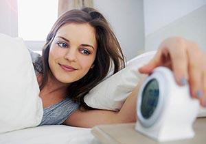 выспавшаяся девушка проснувшись утром  выключает будильник