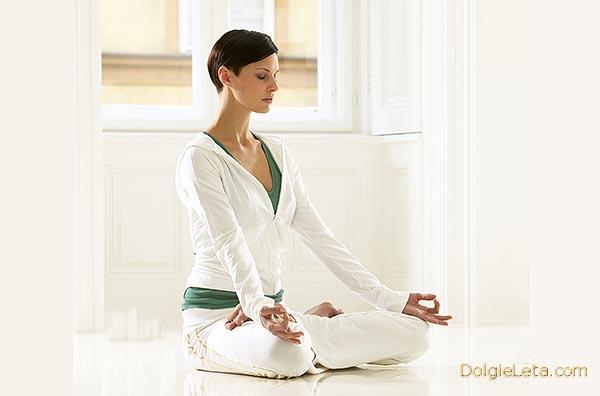 Девушка сидит в позе дзен - дома выполняет упражнения йоги для похудения
