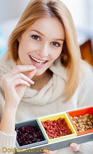 девушка с улыбкой употребляет ягоды годжи