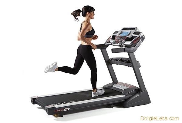 девушка занимается бегом на электрической беговой дорожке