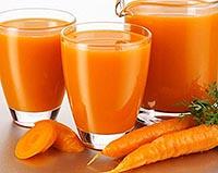 полезный морковный сок в стаканах и кувшине