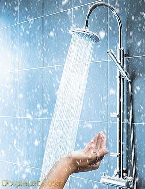 женская рука проверяет температуру воды под душем