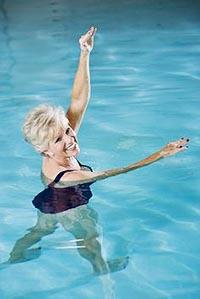 Женщина выполняет упражнения для похудения в бассейне.