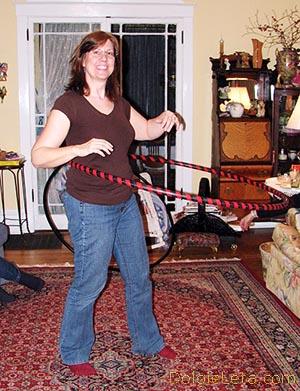женщина крутит обруч в комнате дома