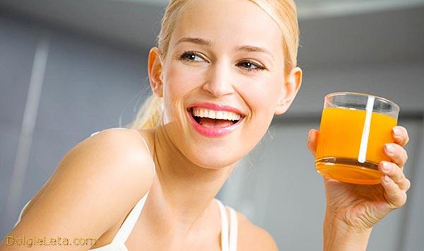женщина пьёт полезный морковный сок