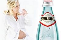 Женщина пьет из стакана минеральную воду Боржоми при беременности.
