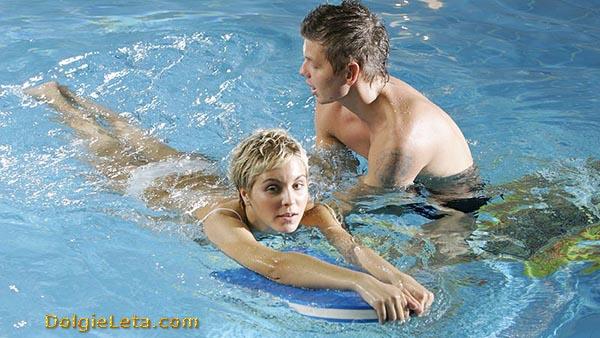Мужчина учит женщину плавать в бассейне с доской
