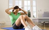 Девушка занимается фитнесом дома: упражнения для пресса.