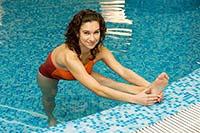Девушка  в бассейне выполняет комплекс эффективных упражнений для похудения.