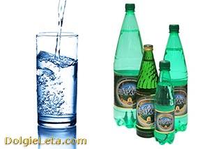 Минеральная вода Нарзан в бутылках и стакане.