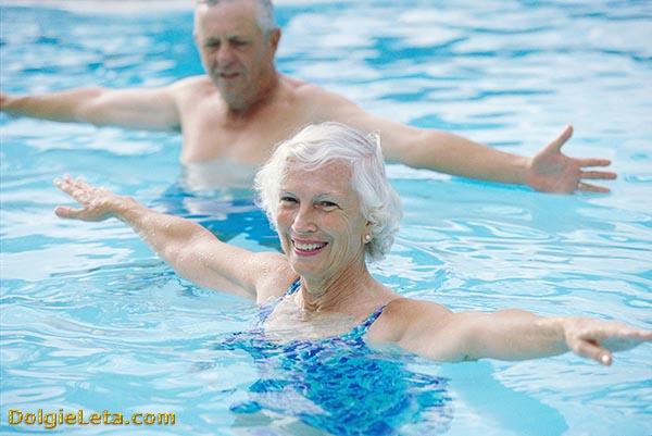 Счастливая пара пенсионеров выполняют упражнения в бассейне