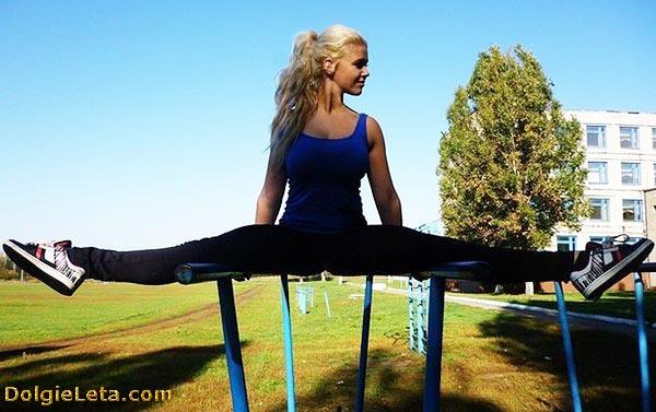 девушка занимается street workout: шпагат на брусьях