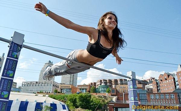 Воркаут: девушка занимается на турнике на улице