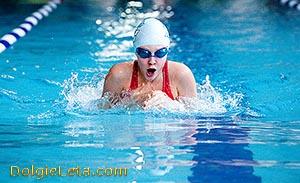 Женщина в бассейне выполняет технику плавания брасом