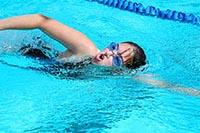 Девушка выполняет технику плавания кролем