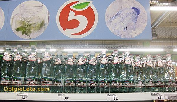 Бутылки с водой на прилавке в магазине Пятерочка.