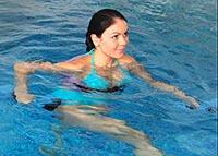 Девушка в бассейне выполняет упражнения для плавания