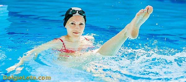 Девушка выполняет в бассейне упражнения для ног и ягодиц