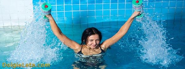 Женщина выполняет упражнения в бассейне для рук