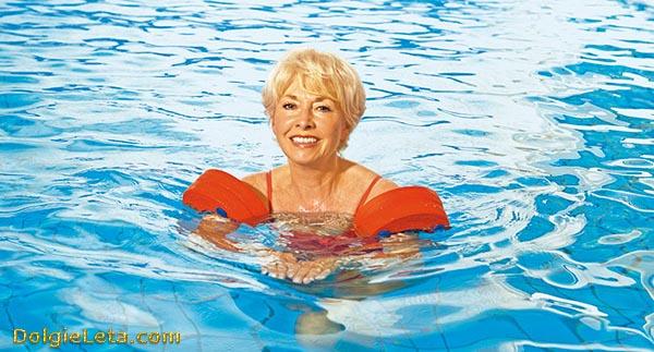 Женщина учится плавать в бассейне с нарукавниками
