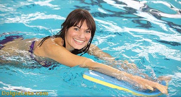 Как правильно плавать в бассейне - женщина учится плавать с доской