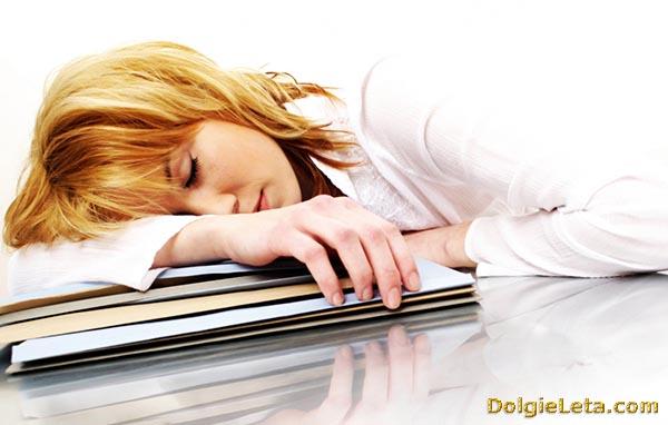Женщина уснула на работе. Признак симптомов хронической усталости.