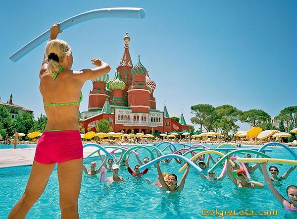 Занятия акваэробикой в открытом бассейне. Спортивные групповые упражнения.
