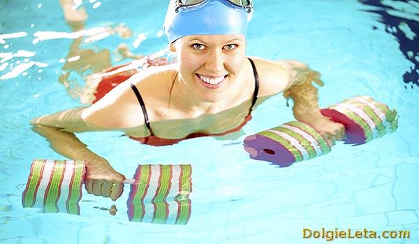 Женщина с гантелями для занятий водным фитнесом.