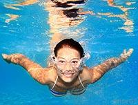 Польза плавания в бассейне для похудения - девушка плывет под водой.