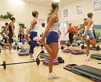 Женщины и девушки тренируются в спортзале, выполняя программу на растяжку.
