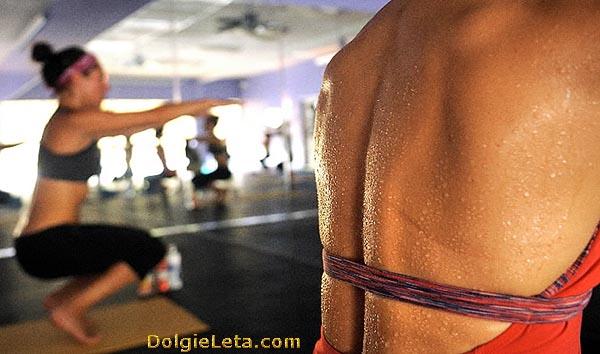 Женщины занимаются горячей йогой в спортивном зале - мокрые от высокой температуры в помещении.