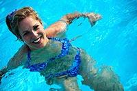 Женщина учится правильно плавать в бассейне.