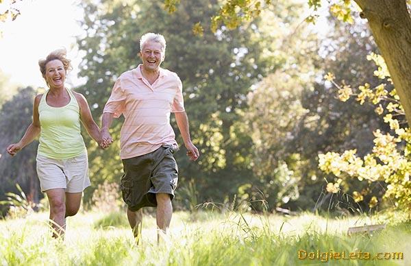 Счастливые муж и жена в возрасте с улыбками, держась за руки, занимаются бегом в парке.