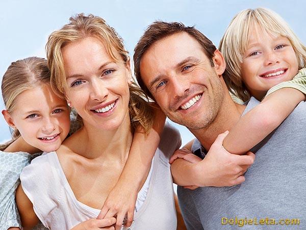На фотографии улыбается вся молодая семья - мама, папа и детишки.