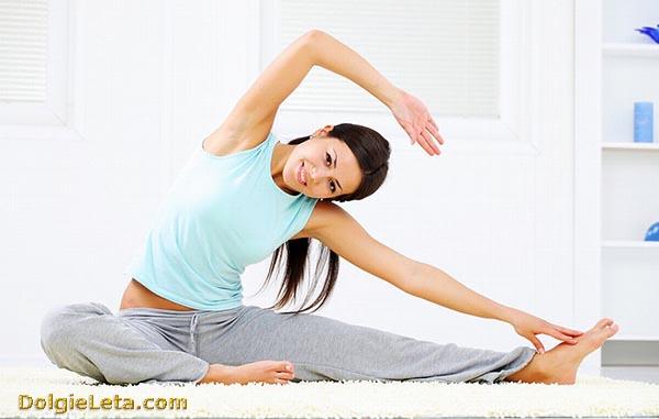 О занятия на растяжку для начинающих - девушка выполняет упражнения.