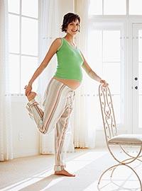 Беременная женщина занимается стретчингом в домашних условиях.