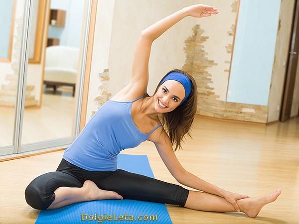 Девушка занимается упражнениями на растяжку в домашних условиях.
