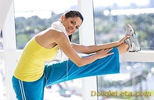 Девушка тренируется стретчингом в домашних условиях.