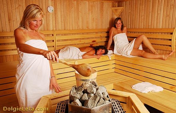 Три девушки греются в бане - одна женщина подкидывает горячую воду на камни печки.