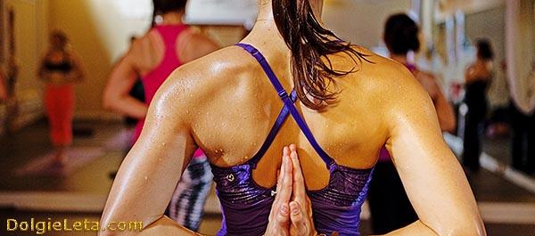 Женщина мокрая от групповых занятий йогой в спортивном зале.