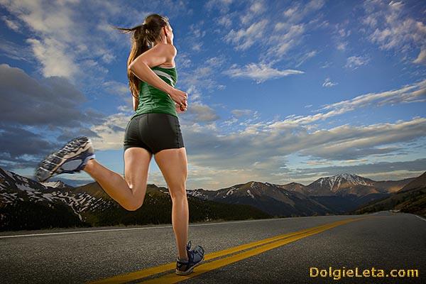 Женщина бежит по асфальтированной дороге.