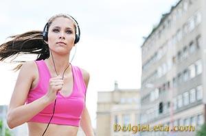 Девушка занимается бегом под музыку в городских условиях.