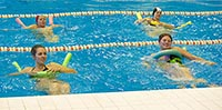 В бассейне занимаются упражнениями по аквааэробике - занятия в воде для похудения.