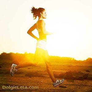 Женщина занимается бегом на природе во время заката солнца для своего здоровья.