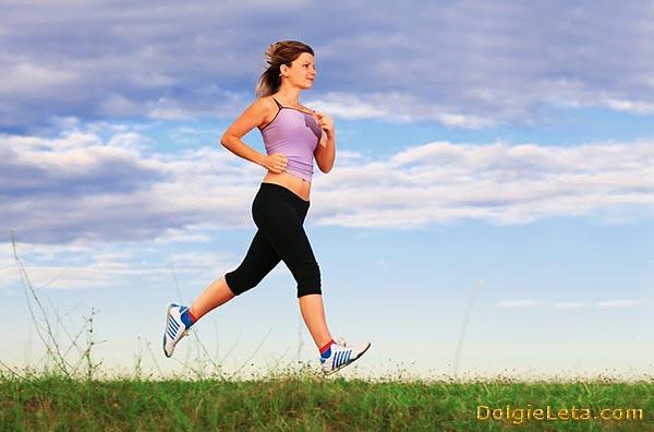 Женщина бежит в парке по полю в траве.