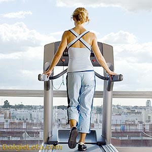 Женщина в домашних условиях занимается бегом на беговой дорожке.