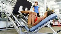 Женщина занимается на тренажере в спортивном зале - выполняет упражнения на тренировку ног.